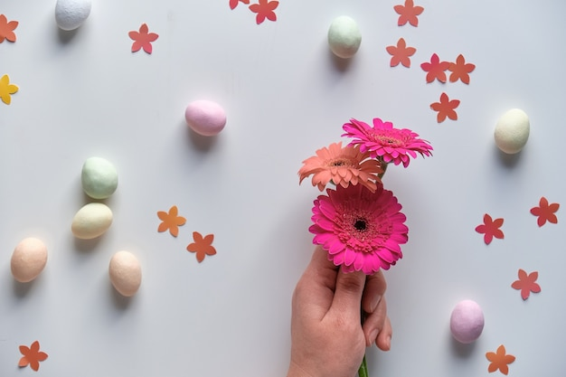 Easter background with gerberas, sweet eggs, flower confetti and colorful felt for craft projects.