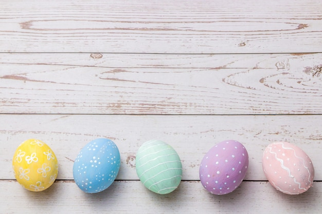 Easter background with hand painted pastel colors eggs on light colored wooden table