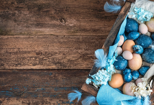 Easter background with marble blue and pastel quail and chicken eggs, decorated with blue feathers