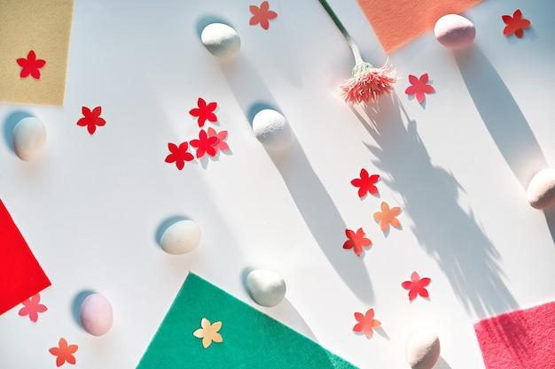 마 지 판 부활절 달걀, gerbera 데이지 꽃, 종이 꽃 색종이와 공예 프로젝트에 대 한 다채로운 느낌의 조각 부활절 배경. 흰색 테이블, 긴 그림자에 평면 위치, 평면도