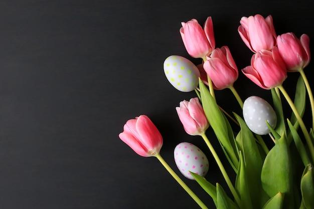 ピンクのチューリップと卵とイースターの背景。春の休日のコンセプト。