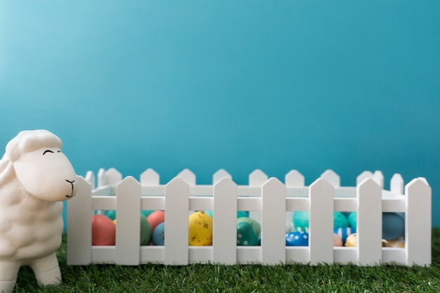 Easter background with sheep next to a wooden fence