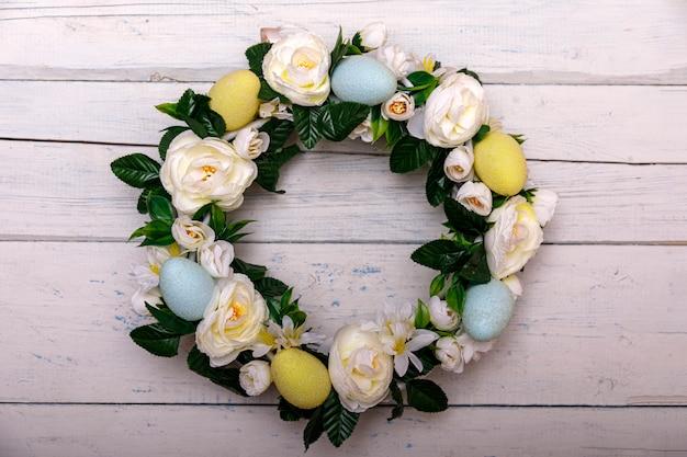 春のイースターエッグと花、ドアに花輪を捧げるとイースターの背景