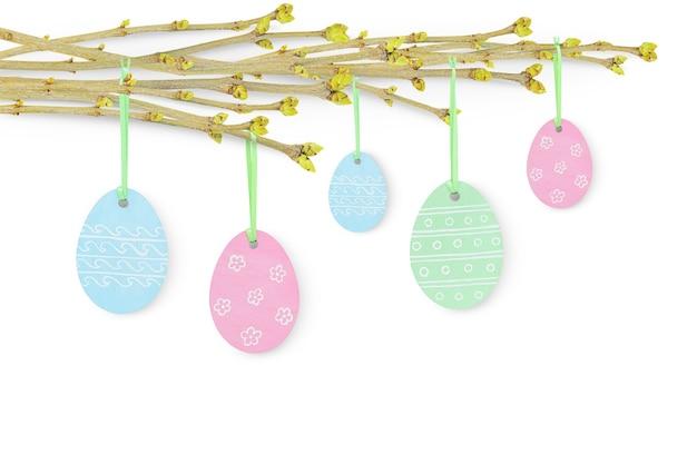 つぼみと白で隔離の塗られた色の卵をぶら下げて若い小枝とイースターの背景