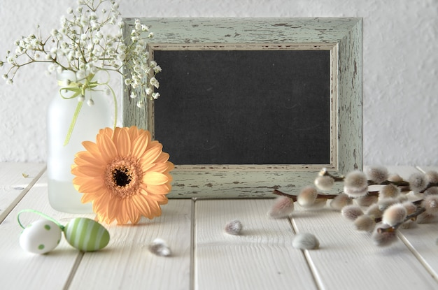 Easter background. yellow herbera and pussy-willow flowers around framed blackboard, text