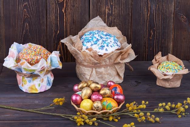 卵と柳の枝を持つイースターベーカリー。暗い木製のテーブルの上の甘いカップケーキ。