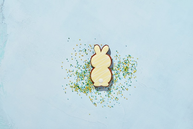 Easter baking background. easter rabbit gingerbread and scattered confectionery topping dressing on blue background.  banner.