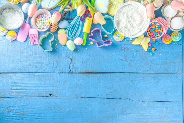 Easter baking background with rolling pin, whisk, eggs, flour and colorful sugar confetti