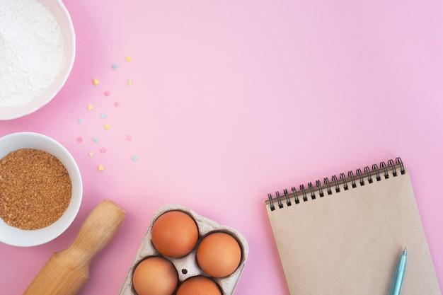 부활절 베이킹 재료와 분홍색 테이블에 메모장. 요리 컨셉과 휴가