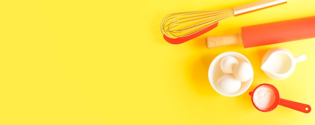 Easter banner for baking. devices and ingredients on a yellow background with copy space.