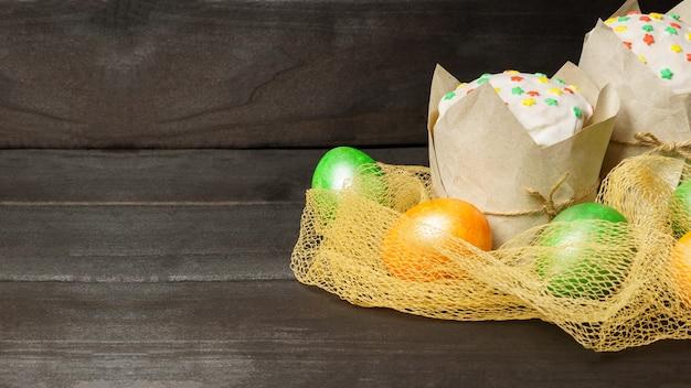 イースターバナーコピースペースのある暗いテーブルに色とりどりのパン粉と色付きの卵で艶をかけられた2つのイースターケーキ