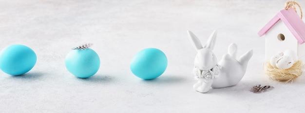 かわいいウサギ、巣、家、青い卵のイースターバナー。