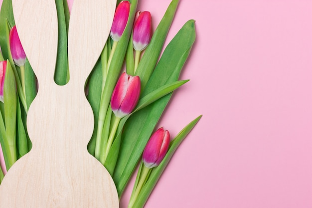 Easter banner with wooden bunny figure and purple fresh tulips. copy space for text
