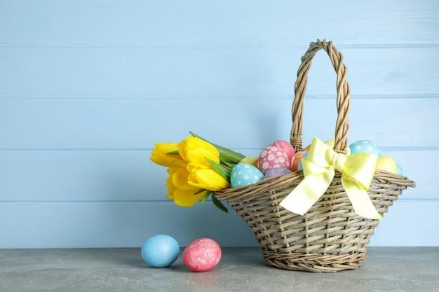 カラフルな卵と木製の背景の花でいっぱいのイースターバスケット