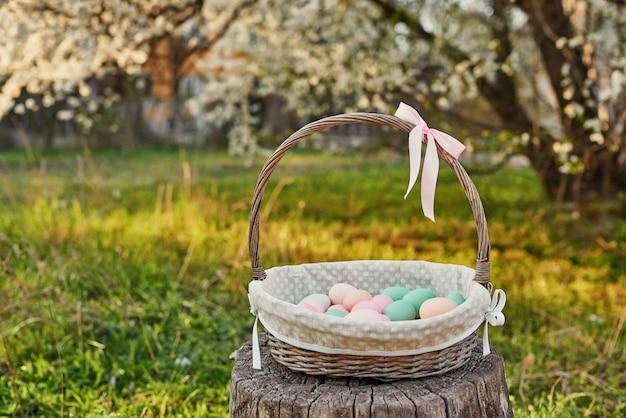 開花木の背景にイースターバスケット。テンプレートイースターのグリーティングカード。イースターエッグと花。卵をイースター装飾。コピースペースで春の休日のコンセプトです。咲く庭