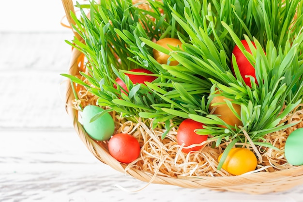 녹색 잔디가 있는 부활절 바구니에는 밝은 색의 부활절 달걀이 가득합니다. 행복한 부활절.