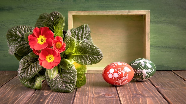 Easter basket with painted easter eggs and red primrose pot flower on rustic wood