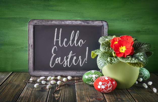 Easter basket with painted easter eggs and red primrose pot flower on rustic wooden wall, text