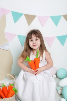 Easter! beautiful little girl in white dress sitting with easter bunnies and carrots. rabbit and colorful eggs. many different colorful eggs, colorful easter interior. agriculture. child and garden.