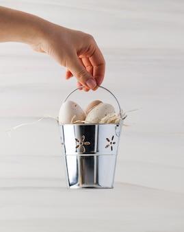 여자 손 부활절 배경에 양동이에 부활절 베이지색 발견 계란