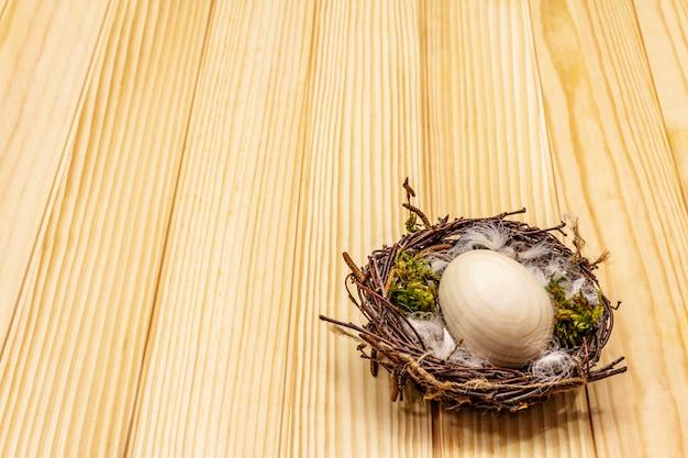 イースターの鳥の巣。廃棄物ゼロ、diyコンセプト。木の卵、羽、苔。ボードの背景