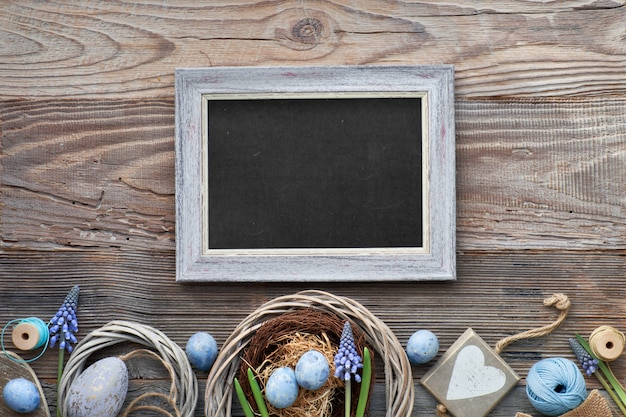 Easter black board with easter eggs, flowers and spring decorations on rustic wood, text