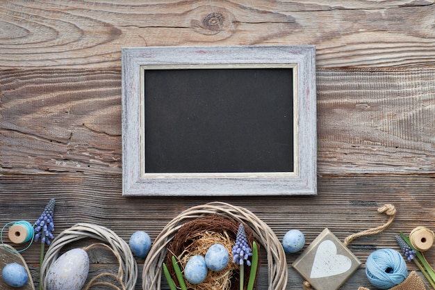 Easter black board with easter eggs, flowers and spring decorations on wood, text space