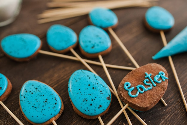 イースターのお祝いのために木の素朴なテーブルにイースターブルーケーキが飛び出します
