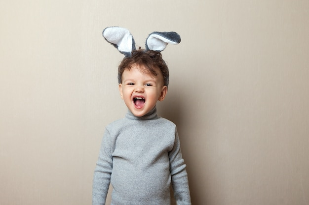Easter. a boy with bunny ears screaming in gray clothes