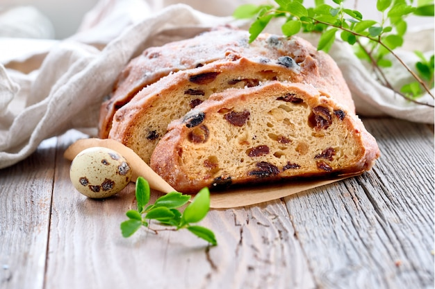 Easter bread, close-up on traditional fruty bread on rustic wood with fresh leaves and quail egg