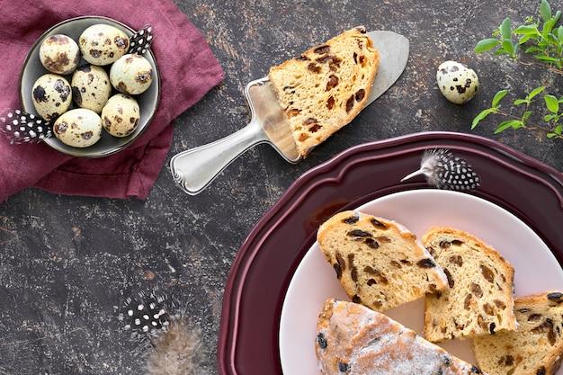 Пасхальный хлеб (остерброт по-немецки). вид сверху традиционного фрутского хлеба на темном столе со свежими листьями и перепелиными яйцами