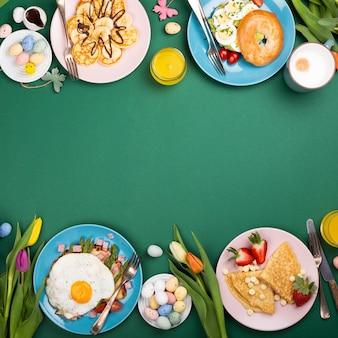 イースター朝食フラットは、スクランブルエッグベーグル、チューリップ、パンケーキ、目玉焼きとグリーンアスパラガスのパントースト、色付きのウズラの卵、春の休日の装飾で横たわっていました。上面図。コピースペース