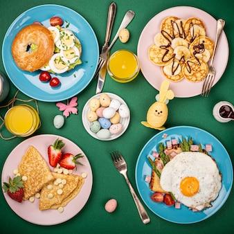 イースター朝食フラットは、スクランブルエッグベーグル、チューリップ、パンケーキ、目玉焼きとグリーンアスパラガスのパントースト、色付きのウズラの卵、春の休日の装飾で横たわっていました。上面図