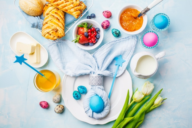 Easter breakfast table. colored eggs, bun, juice and jam. blue background, top view, flat lay.
