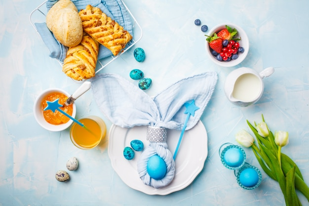 Easter breakfast table. colored eggs, buns, juice and jam. blue background, top view, flat lay.