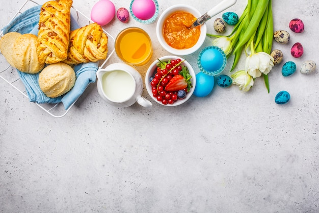 Easter breakfast table, top view. colored eggs, flowers, buns, milk, juice and jam, white background.
