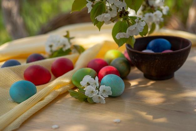 부활절 브런치 야외. 다채로운 계란, 나무 테이블에 꽃이 만발한 벚꽃 가지