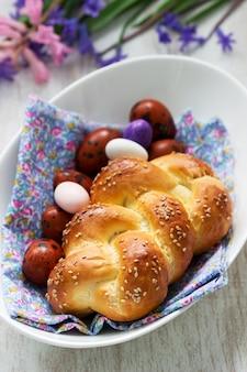 イースターのパン、着色された卵、白い背景の上に花。