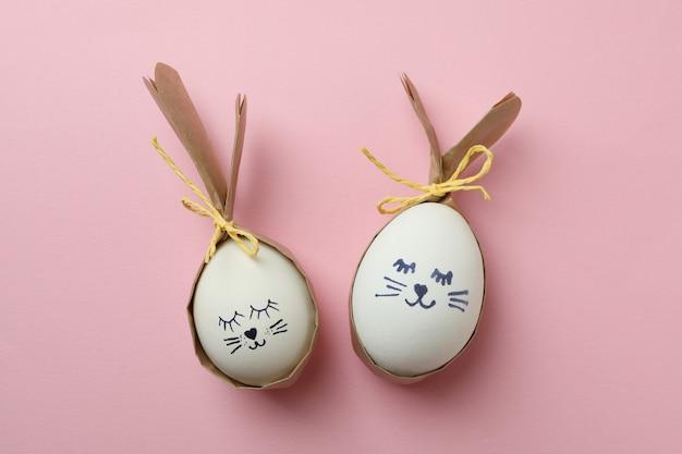 분홍색 배경에 계란으로 만든 부활절 토끼
