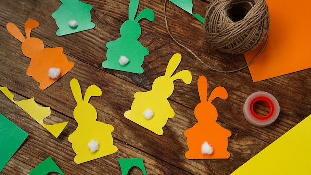 Easter bunnies made of paper on a wooden surface