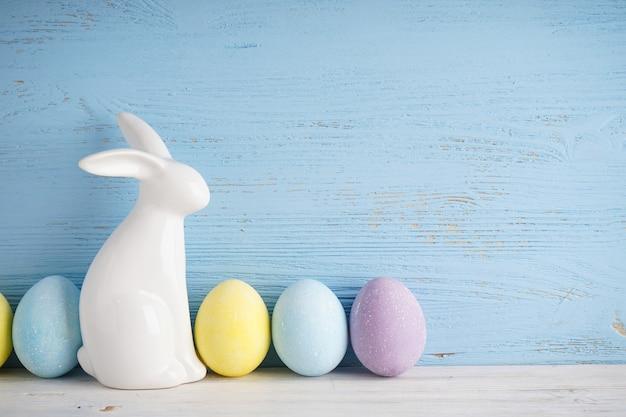 Пасхальный кролик и красочные яйца на синем деревянном фоне