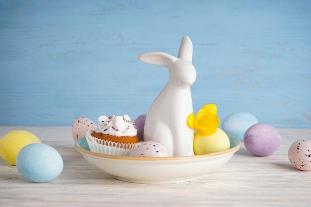 Пасхальный кролик и яйца с цветком на деревянном фоне