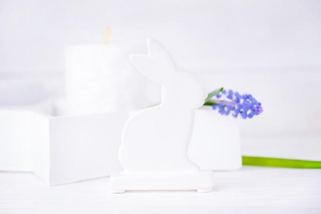 Пасхальный заяц и виноградный гиацинт, белое фото с синим цветком мускари
