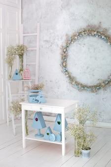 Пасхальный кролик, синие скворечники, букет цветов на кухонном столе Premium Фотографии