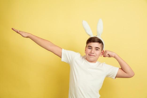 黄色の壁に明るい感情を持つイースターのウサギの少年