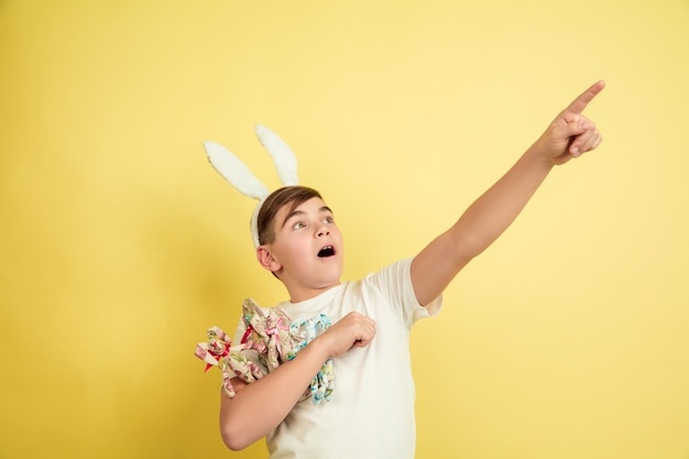 Easter bunny boy with bright emotions on yellow studio wall