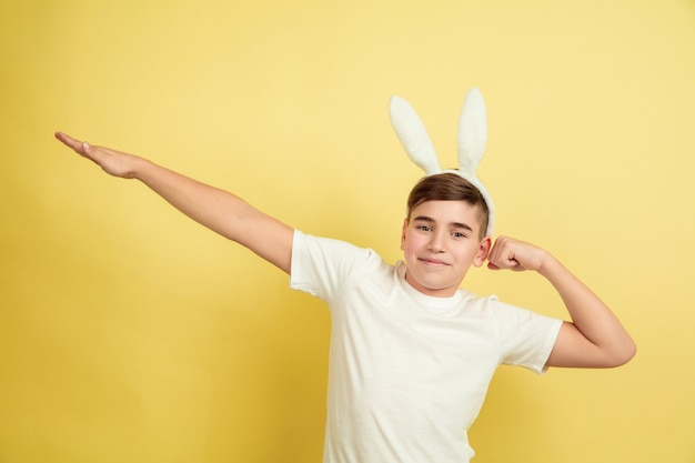 Ragazzo del coniglietto di pasqua con emozioni luminose sulla parete gialla