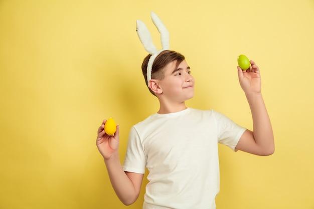 Ragazzo del coniglietto di pasqua con emozioni luminose su giallo
