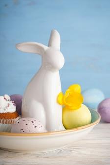 Пасхальный заяц керамический и яйца с цветком на деревянном фоне.