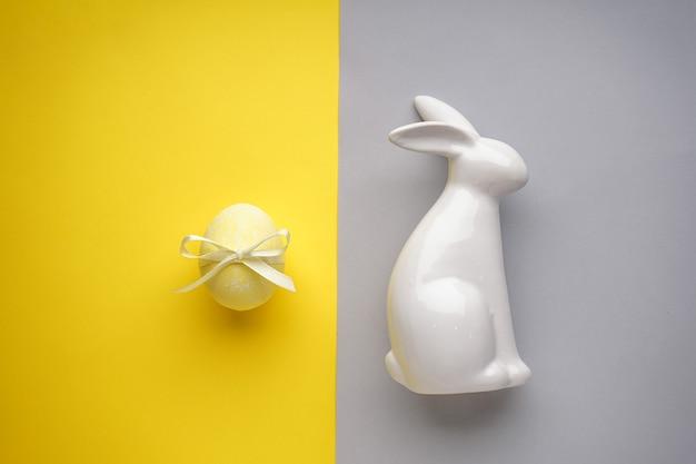 Пасхальный заяц керамический с желтым пасхальным яйцом с лентой на желто-серой поверхности, плоская планировка.